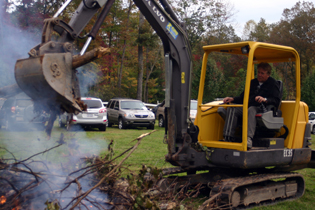 Mike uses heavy equipment to add more wood to the spectacular bonfire.